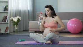 Senhora nos estados finais de gravidez que fazem a ioga, água potável, parto seguro video estoque
