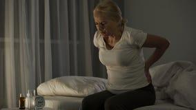 A senhora nos seus 50 não pode dormir devido à dor aguda em uma mais baixos parte traseira e rins, saúde video estoque