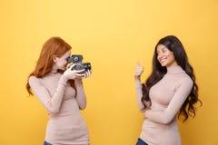 Senhora nova alegre do ruivo que fotografa a mulher africana fotografia de stock