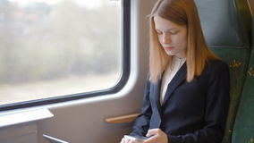 A senhora nova do negócio está trabalhando em seu portátil e está usando seu telefone no trem video estoque