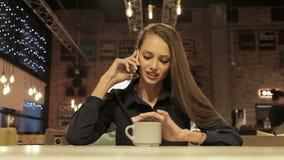 Senhora nova do negócio que fala em um telefone celular que senta-se em uma tabela em um café video estoque