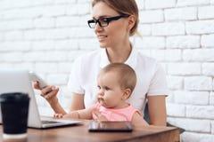 A senhora nova do negócio tenta trabalhar com bebê imagens de stock