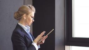 A senhora nova do negócio toma notas na tabuleta que está na janela de um escritório moderno filme