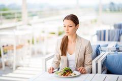 A senhora nova pensativa do negócio está tendo seu almoço na parte superior do telhado imagens de stock royalty free