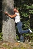 Senhora nova que abraça a árvore fotos de stock