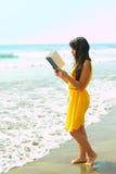 Senhora nova que lê um livro na praia Imagens de Stock Royalty Free