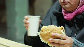 Senhora pobre que aprecia o almoço da caridade, comendo o hamburguer e bebendo o chá quente no abrigo vídeos de arquivo