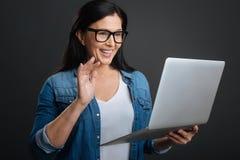 Senhora positiva amigável que usa a tecnologia moderna para uma comunicação Fotografia de Stock