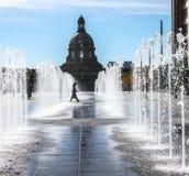 Senhora que anda através da água na frente da construção legislativa Imagem de Stock Royalty Free