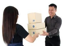 Senhora que cede uma pilha de pacote a um homem de negócios feliz isolado no fundo branco fotos de stock