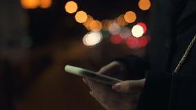 Senhora que chama o táxi usando a posição perto da estrada, iluminação da aplicação do telefone filme