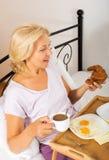 Senhora que come o café da manhã no quarto Imagens de Stock