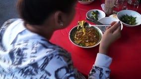 Senhora que come a sopa de macarronete do mami ao longo do passeio de uma rua da cidade vídeos de arquivo