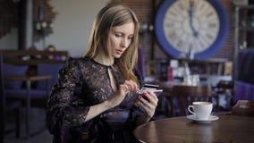 Senhora que compra em linha com um cartão de crédito e um smartphone que sentam-se no restaurante com os povos no fundo Mulher no video estoque