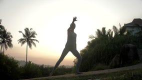 Senhora que faz exercícios da ioga na trilha no movimento lento do nascer do sol filme