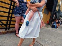 A senhora que guarda um bebê anda ao longo do passeio enquanto uma outra mulher se inclina contra uns trilhos fotografia de stock
