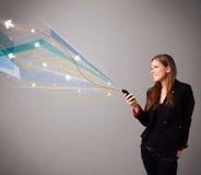 Senhora que guardara um telefone com linhas abstratas coloridas Foto de Stock Royalty Free