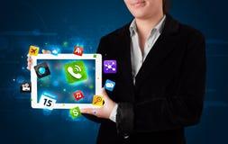 Senhora que guardara uma tabuleta com apps e ícones coloridos modernos Imagem de Stock