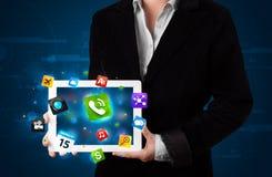 Senhora que guardara uma tabuleta com apps e ícones coloridos modernos Fotos de Stock