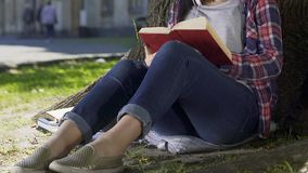Senhora que lê a novela romântica no parque, preocupando-se sobre heróis do livro, o melhor vendedor vídeos de arquivo