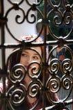 Senhora que olha através das barras ornamentados imagem de stock royalty free