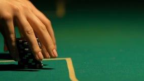 Senhora que põe fileiras da microplaqueta de pôquer sobre a tabela, a aposta do casino, a possibilidade da vitória e a fortuna video estoque