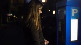 Senhora que põe moedas no medidor de estacionamento, andando ao carro, serviço do transporte filme