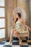 Senhora que senta-se na cadeira do vintage Fotografia de Stock Royalty Free