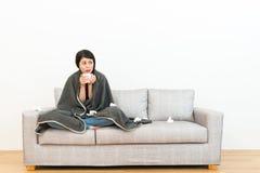 Senhora que senta-se no sofá do sofá e que guarda a água quente Imagens de Stock
