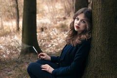 Senhora que senta-se perto da árvore Fotografia de Stock