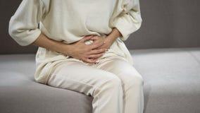 Senhora que sofre da dor de estômago forte, gastrite, problemas com bexiga de bílis imagem de stock