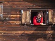 Senhora que sorri da janela Imagem de Stock Royalty Free