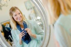 Senhora que tenta no lenço que olha a reflexão no espelho imagens de stock royalty free