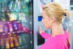 Senhora que usa uma máquina de venda automática moderna Fotografia de Stock