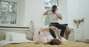 Senhora rústica do quarto do estilo na cama que levanta para seu noivo que está fazendo imagens para memórias Disparado na epopei filme
