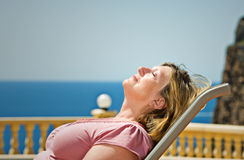 Senhora sênior Sunbathing de encontro ao contexto litoral fotos de stock royalty free
