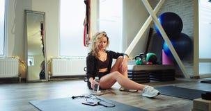 Senhora sedento após um exercício duro do gym que sentam-se para baixo no assoalho que bebe alguma água e o pneu têm uma estadia  vídeos de arquivo