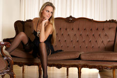 Senhora 'sexy' que desgasta a roupa interior erótica em um sofá Imagem de Stock Royalty Free