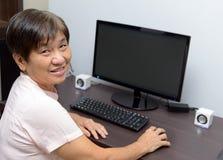 Senhora superior com computador de secretária imagens de stock royalty free
