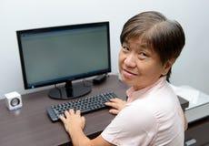 Senhora superior com computador de secretária fotografia de stock royalty free