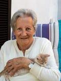 Senhora superior com o cabelo branco, guardando o gatinho do gengibre do salvamento Fotografia de Stock