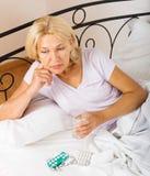 Senhora superior com os comprimidos na cama Imagem de Stock