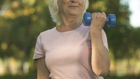 Senhora superior de sorriso que faz exercícios de braço com peso, pesos de levantamento, força vídeos de arquivo