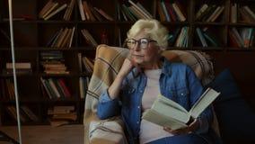 Senhora superior deleitada que lê um livro em casa filme