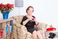 Senhora superior feliz que aprecia sua confecção de malhas Fotos de Stock Royalty Free