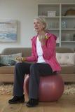 Senhora superior que exercita em casa Fotos de Stock Royalty Free