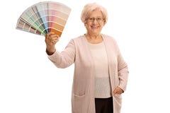 Senhora superior que guarda uma amostra de folha da cor imagem de stock