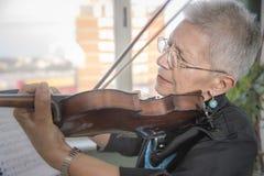 Senhora superior que joga o violino fotografia de stock
