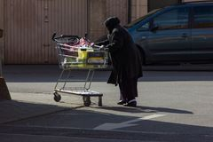 senhora superior turca muçulmana do estrangeiro com carrinho de compras fotografia de stock royalty free