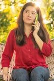 A senhora tailandesa bonita está falando no telefone celular a uma comunicação Fotos de Stock Royalty Free